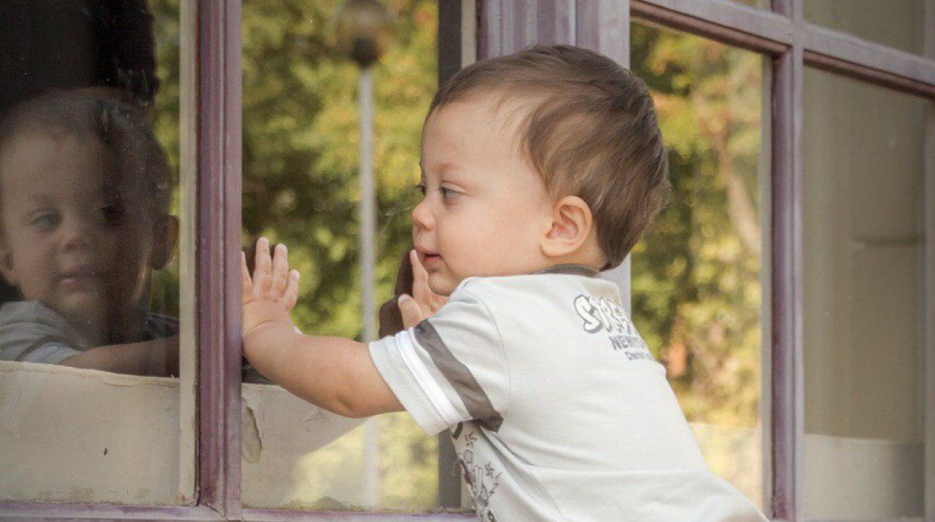 Kisgyermek nézi önmagát a tükörben.