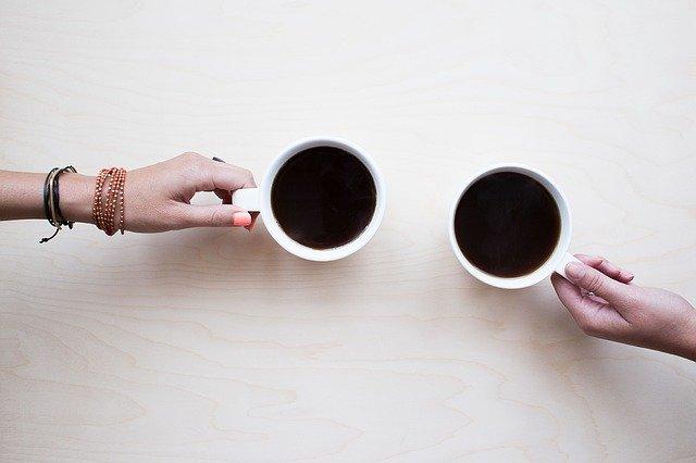 Két csésze kávé két barátnő kezében
